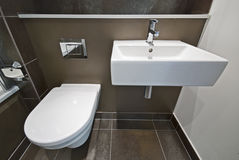 Bathroom detail with toilet and wash basin. Detail of a modern en suite bathroom with ceramic toilet, wash basin in brown Royalty Free Stock Images