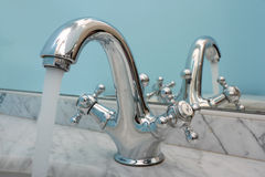 Bathroom faucet. Water running from an open water faucet Royalty Free Stock Images