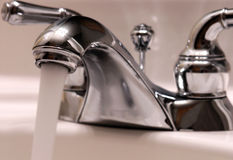 Bathroom Faucet. A running bathroom faucet.  Focus on the head of the faucet and the running water Stock Photography