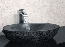 Bathroom faucet and black stone sink Royalty Free Stock Images