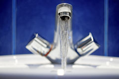 Bathroom faucet. Water flow from chromed steel Stock Image