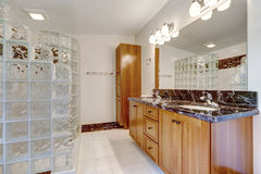 Bathroom with glass block screened shower. Brown cabinet with black granite top and large mirror Royalty Free Stock Image