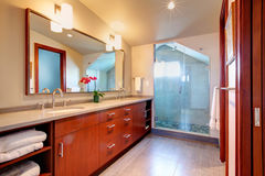 Bathroom with glass door shower. Bright bathroom with bright brown cabinets, mirror, glass door shower with vaulted ceiling royalty free stock photos