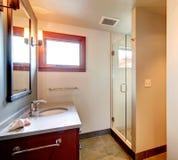 Bathroom with glass door shower. Bright bathroom with cherry washbasin cabinet, mirror, glass door shower stock photos