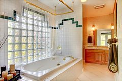 Bathroom with glass wall and tub. With wood cabinets and candle Royalty Free Stock Images