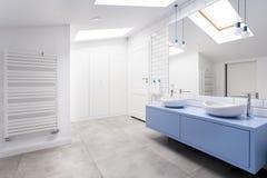 Bathroom with grey floor. Cozy attic bathroom with grey floor, blue washbasin cabinet and heater Royalty Free Stock Photos