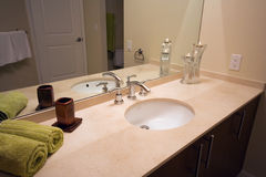 Bathroom interior. Interior of a new modern bathroom. Wooden cabinets, marble counter top, large mirror and chrome faucet Stock Photo