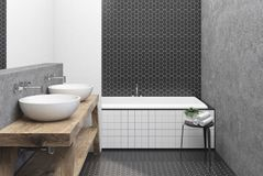 Hexagon tile white and black bathroom, tub. Bathroom interior with black hexagon tile and concrete walls, a large angular tub and a double sink on a wooden shelf stock illustration