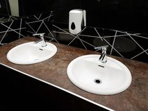 Bathroom interior in black and white. Round ceramic washbasins. Mirrors, plastic soap dish and chrome faucets for washing hands af. Ter a toilet. Design with stock photography