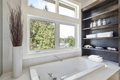 Bathroom interior with a drop in tub. A white drop in tub fitted with wooden shelves with stacked towels and white seashells sits beneath a window with a stock images