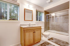 Bathroom interior with screened bath tub. Bathroom interior with glass screened bath tub. Brown cabinet with mirror Stock Photography
