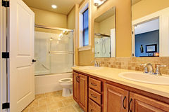 Bathroom interior with screened bath tub. Soft tones bathroom interior. View of wooden bathroom vanity cabinet with two sinks and glass screened bath tub Royalty Free Stock Images