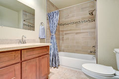 Bathroom interior with vanity cabinet and blue shower curtain. Royalty Free Stock Photography