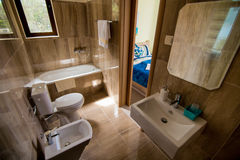 Free Bathroom Interior - Washbasin, Bidet, Toilet, Large Mirror. The Walls Are Light Brown In Color. Stock Images - 90802404