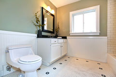 Bathroom interior with white tile, plank wall trim, green walls, Royalty Free Stock Photo