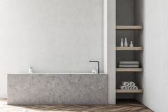 White bathroom interior, marble tub. Bathroom interior with a wooden floor, white walls, a marble angular tub and shelves in the corner. 3d rendering mock up royalty free illustration