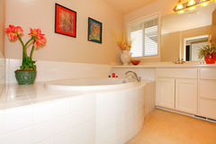 Bathroom with large round white tub. And cabinets with double sink stock photography