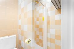 Bathroom with shower, toilet bowl and sink. Hotel standart bedroom. simple and stylish interior. interior lighting. Bathroom with large shower, toilet bowl and stock images