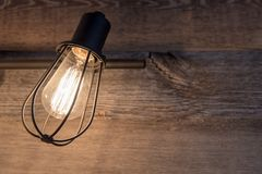 Bathroom lighting with rustic metal light bulb cage on a background of weathered wood. Close up photograph of bathroom lighting with rustic metal light bulb cage royalty free stock photo