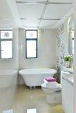 Bathroom. A lovely  white tiled family bathroom with a large bathtub Stock Photos