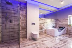 Bathroom with marble tiles and glass shower cabin. Spacious bathroom with marble tiles, toilet, hot tub and glass shower cabin Royalty Free Stock Photos
