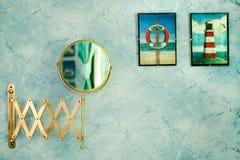 Bathroom Mirror. A bathroom shaving mirror against blue wallpaper in the bathroom royalty free stock images