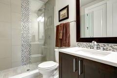 Bathroom modern interior with dark hardwood cabinets and glass door shower. In luxury home stock photography