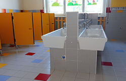 Bathroom of the nursery school with ceramic sinks. Inside the bathroom of the nursery school with white sinks and doors yellow stock photography