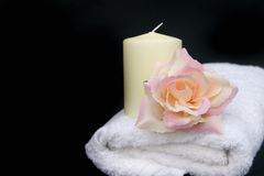 Bathroom pampering. Refreshing spa luxury with candle, rose and white spa towel Stock Photography