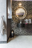 Bathroom with pattern wallpaper, sparkle floor. New bathroom with pattern wallpaper, sparkle floor, round mirror with decorative golden frame and black basin stock photos