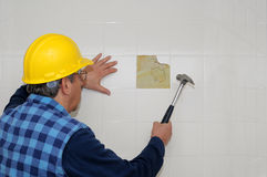 Bathroom renovation. Worker breaking up bathroom tiles Stock Photo
