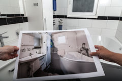 Bathroom renovation. A man and a woman hands are together holding a photograph that shows a bathroom before and after renovation. The scene takes place in the Royalty Free Stock Image