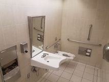 Bathroom toilet with paper and metal railings and sink. Bathroom or restroom toilet with paper and metal railings and sink royalty free stock photos
