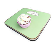 Bathroom scale with the cupcake Royalty Free Stock Photos