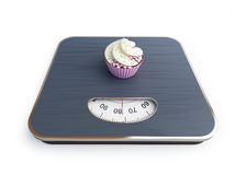 Bathroom scale with the cupcake a white background Royalty Free Stock Photos