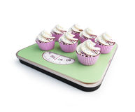 Bathroom scale with the cupcakes. On a white background Royalty Free Stock Photography