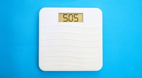 Bathroom scale, display sos. White bathroom scale on a blue background Royalty Free Stock Photos