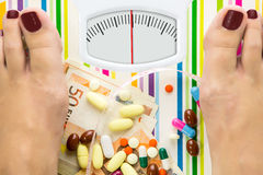 Bathroom scale with pills and money Royalty Free Stock Photo