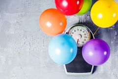 Bathroom scales with colorful balloons. Slimming concept stock photos