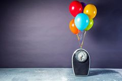 Bathroom scales with colorful balloons. Slimming concept stock photography
