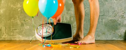 Bathroom scales with colorful balloons. Slimming concept royalty free stock image