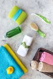 Bathroom set. Towels, bottles with soap and shampoo, cobs on grey stone backgrond top view Stock Photo