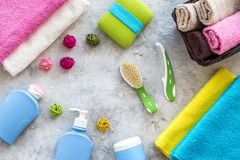 Bathroom set. Towels, bottles with soap and shampoo, cobs on grey stone backgrond top view Stock Photography