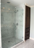 Bathroom Shower. A simple bathroom shower is all glass with a dark wood cabinet next to it Royalty Free Stock Photo