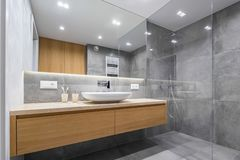 Bathroom with shower and mirror. Modern bathroom with wooden countertop, shower, basin and big mirror stock image