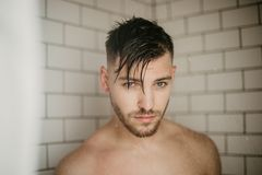 Young Attractive Male Model Washing Hair in Trendy Modern Subway Tile Wet Shower royalty free stock photo