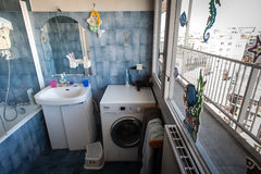 A bathroom. With a shower, a sink, a closet, a mirror, a washing machine and stickers on the window alongside a balcony Stock Photos