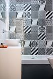 Bathroom with shower unit, toilet, bidet and basin unit, with black and white monochrome patchwork tiles and high ceiling. Bathroom with shower unit, toilet royalty free stock photo