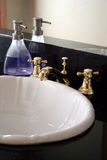 Bathroom Sink. Some purple soap sits next to a bathroom sink with black marble stock images