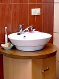 Bathroom sink. Modern bathroom with sink and wooden cupboard below stock photos